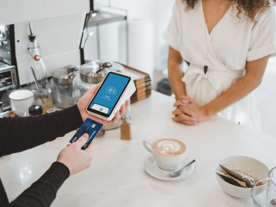 Barista putting Credit Card with a chip into a phone to pay.