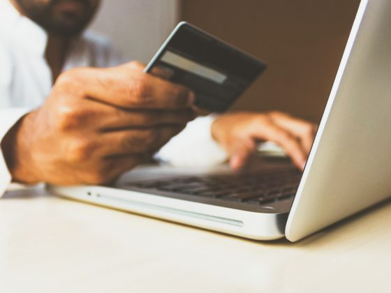 Close up of man's hand holding a credit card near his laptop