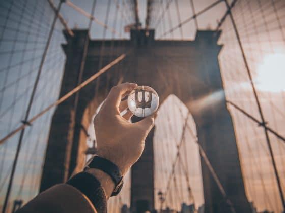 man holding ball facing Brooklyn Bridge, New York. Establishing a new perspective
