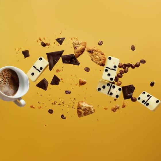 dominos and coffee falling with a yellow background