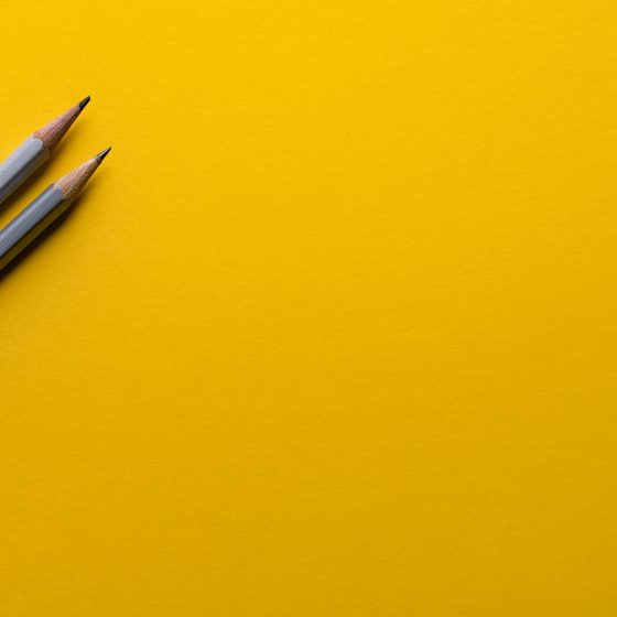 2 sharpened pencils against a yellow background