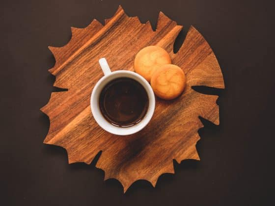 cup of coffee with two cookies on a maple leaf shaped cutting board against a brown background