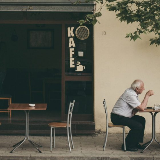 Two men sitting at a table outside of a cafe in Durrës, Albania