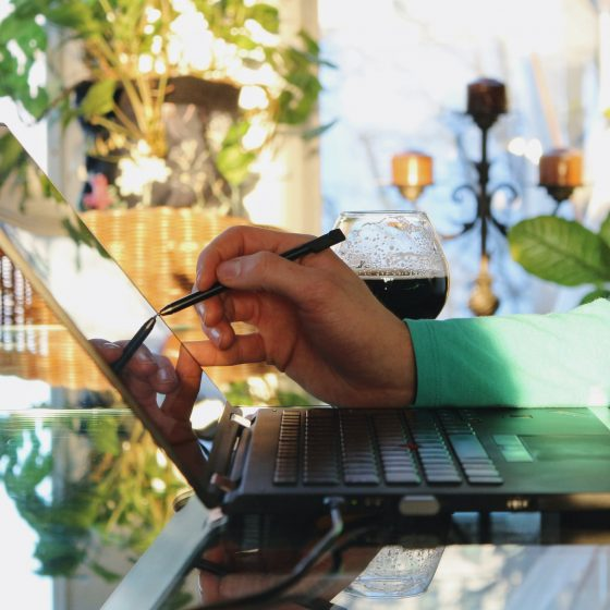 Young professionnal working from home using a touchscreen laptop with his stylus with a bright sunny light and plants in the background.